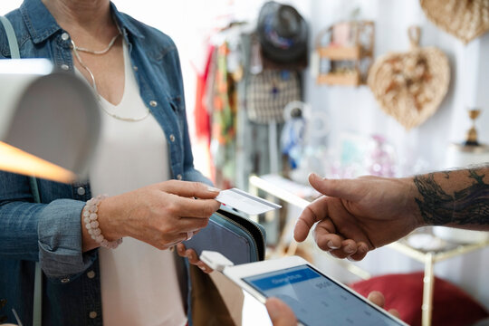 Woman shopping at bazaar marketplace, paying with credit card