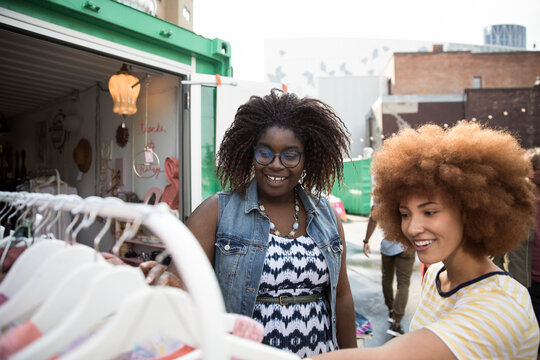Smiling young women friends shopping for clothes at bazaar market