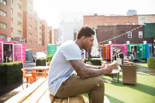 Young man using smart phone at sunny urban bazaar market