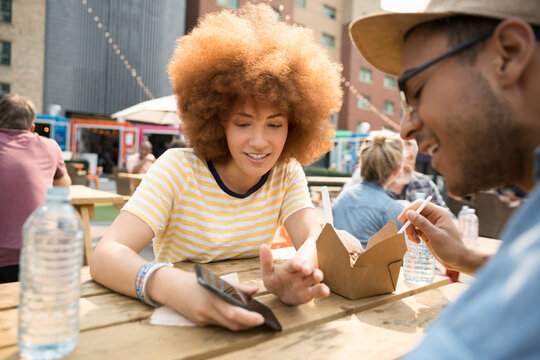 Couple with smart phone eating at urban bazaar marketplace