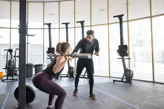 Personal trainer guiding woman doing barbell squats in gym