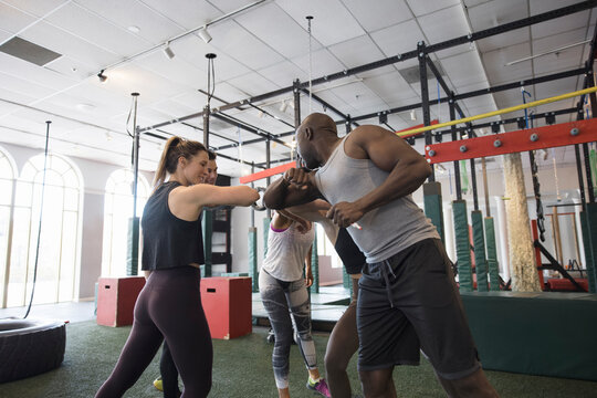 Cross training class elbow bumping in circle in gym