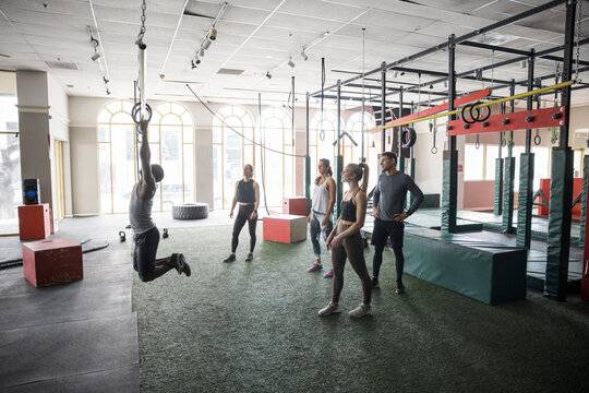 Cross training class watching instructor demonstrate pull ups on rings