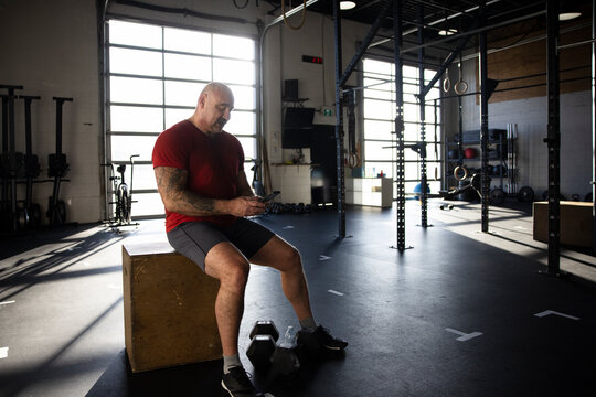 Mature man taking break from workout with smart phone in gym