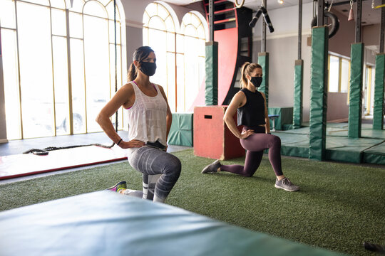 Women in face masks doing lunge stretches in gym