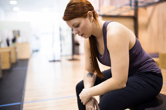 Tired woman taking a break from workout in gym