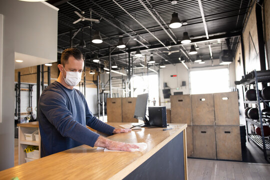 Male gym owner in face mask sanitizing front desk counter