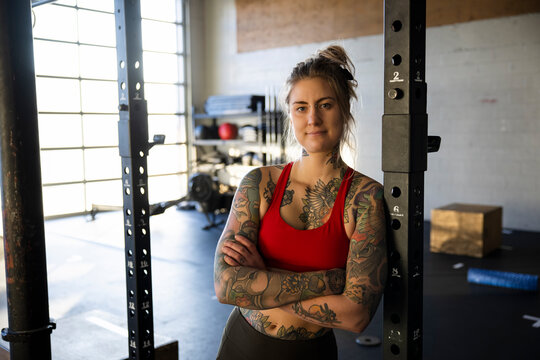 Portrait confident woman with tattoos working out in gym