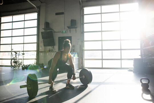 Young woman exercising with barbell in sunny cross training gym