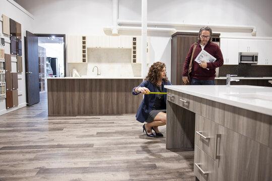 Saleswoman measuring worktop in kitchen showroom