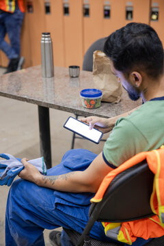 Worker using phone at lunch break in locker room