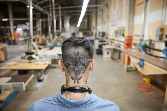 Rear view of tattoo on worker's head in distribution warehouse