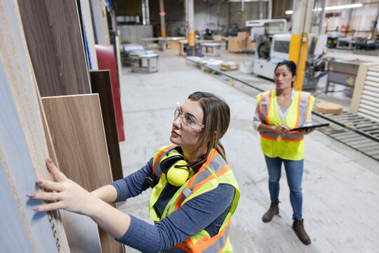 Workers inspecting wooden boards in distribution warehouse