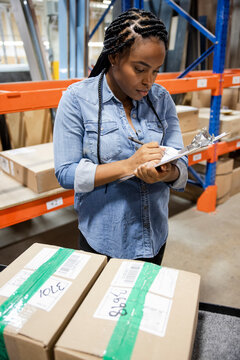 Worker checking stock list in distribution warehouse
