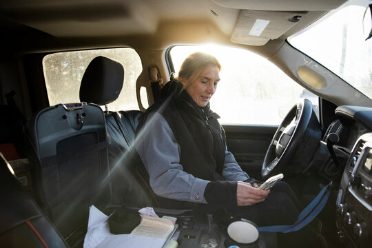 Woman working with phone inside vehicle