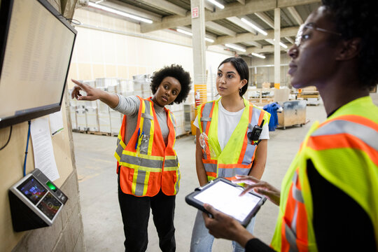 Colleagues working with digital devices in distribution warehouse