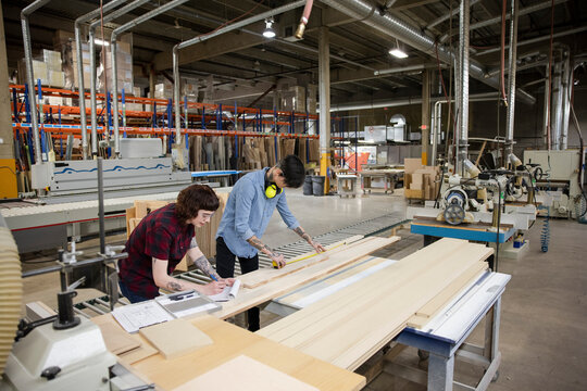 Colleagues measuring wooden panels in distribution warehouse