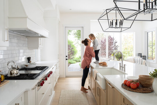 Mother and toddler daughter kissing in home showcase interior kitchen