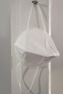 Uma máscara de proteção, na cor branca, pendurada após o uso.