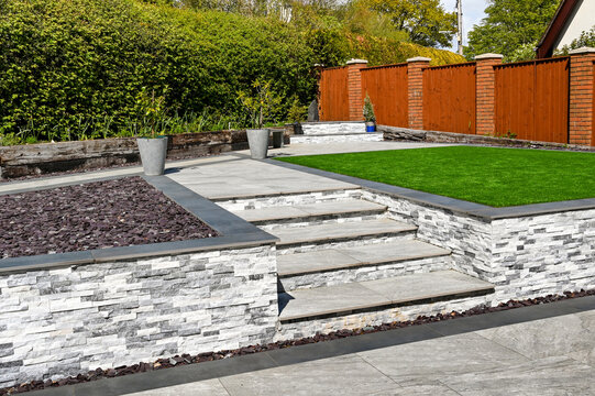 Steps from a patio to path and artificial grass in a residential back garden landscaped with light and dark grey porcelain paving slabs. No people.