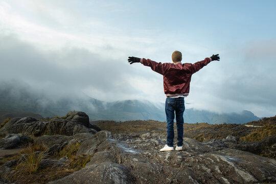 Hombre joven parado en la cima de una montaña con los brazos abiertos mirando el paisaje con la nubes azules de fondo