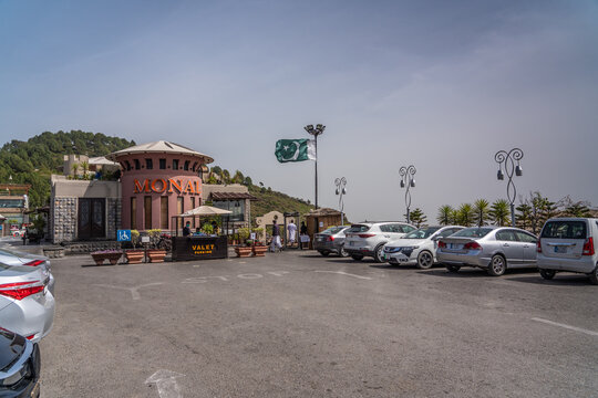 """Islamabad, Pakistan, March 2021, entrance and parking area for """"The Monal Restaurant at Margalla Hills in Islamabad mountain range with the Pakistan flag dancing in the wind"""