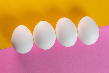 Eggs on the yellow and pink background