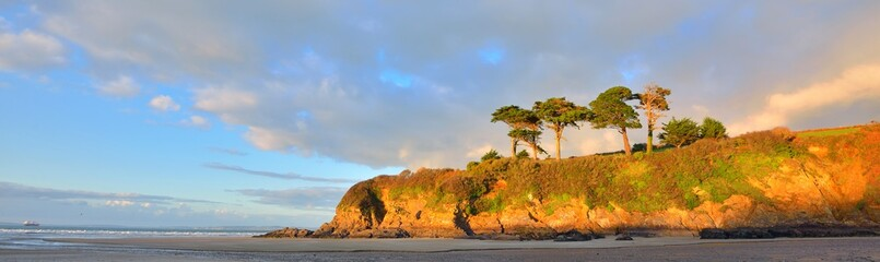 Orange cliff with tall trees on the coast of bay of Douarnenez. Blue sky with colorful evening clouds. Reflections on the water. Brittany, France - fototapety na wymiar