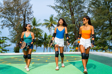 Group of Happy Asian woman girl friends carry skateboard walking with talking together at skateboard park. Female friendship enjoy outdoor activity lifestyle play extreme sport surf skate together