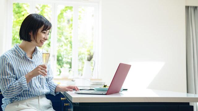 キッチンでパソコンを見ながら食事する女性 オンライン飲み会 サークルショット