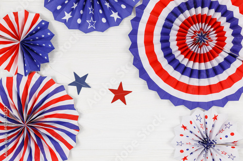 Decorations for 4th of July day of American independence, flag,  straws, paper fans. USA holiday decorations on a white wooden background, top view, flat lay
