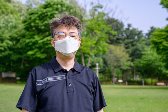 Middle-aged Asian male wearing a face mask on the lawn.