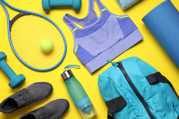 Flat lay composition with sports equipment on yellow background