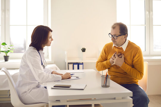 Senior male patient at a cardiologist's appointment talks about his pain in the heart area. Female doctor listens intently to the patient sitting at a table in his office. Concept of medical advice.
