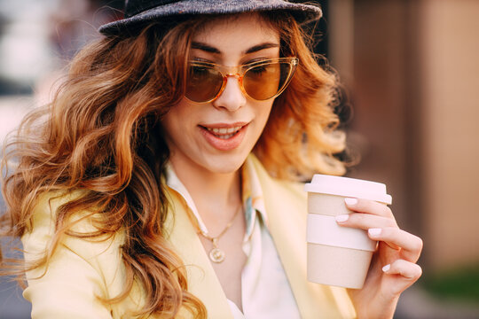 Portrait of young woman with curly hair and sunglasses holding coffee cup