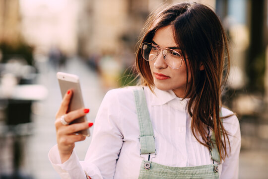 Portrait of young woman with sunglasses using mobile phone