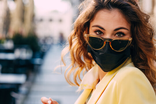 Portrait of young woman with protective face mask and sunglasses