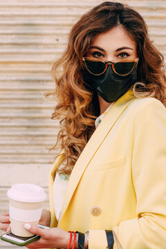 Portrait of young woman with protective face mask and sunglasses holding takeaway coffee cup