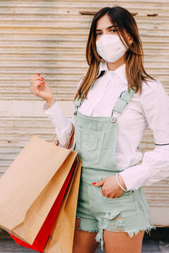 Portrait of young woman with protective face mask, sunglasses and shopping bags