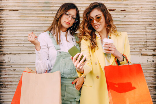 Two happy young women with shopping bags using mobile phone