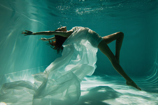 barefoot woman in white elegant dress swimming in pool