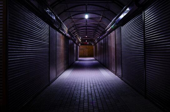 closed market steel roller shutters. night lane. street vendors