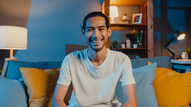 Happy young freelance asian man looking at camera smile and talk with friends on video call online at night in living room at home, Stay at home quarantine, work from home, Social distancing concept.