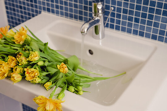 A bouquet of fresh yellow tulips with green stems in a sink with water running from the faucet in a modern bathroom decorated with blue tile.