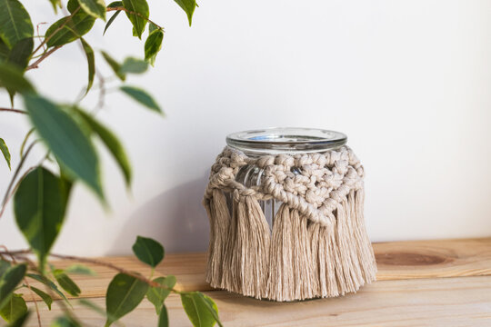 Beautiful jar candle holder with macrame decor on wood shelf. Boho home decor. Houseplant in front. Rustic decoration.