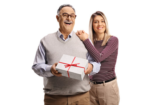 Young woman hugging a smiling mature man with a present box