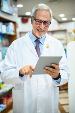 Senior pharmacist working on tablet in his store