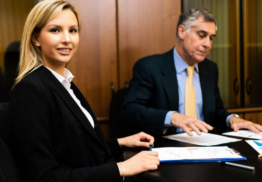 Two businesspeople discussing sitting at desk in their office