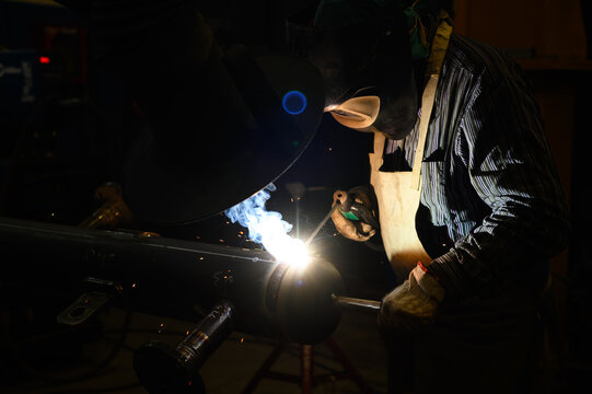Worker operating an angle grinder and making lots of sparks