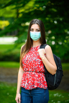 Female student walking outdoor in the park and wearing a mask to protect herself from coronavirus